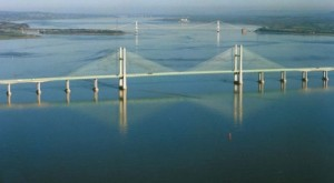 A wide angle shot looking upstream from the Estuary, with the Second Severn Crossing in the foreground and the older Severn Bridge behind it